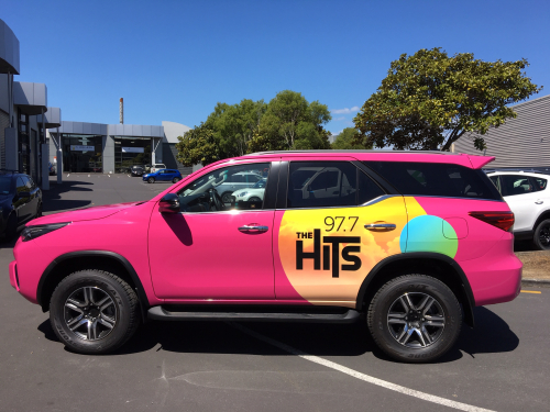 Hot pink vehicle graphics for The Hits.